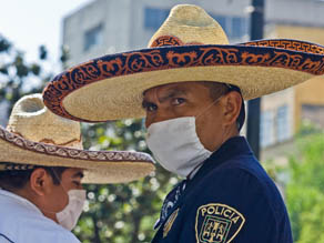 Mexican police stand guard wearing surgery masks in Mexico City