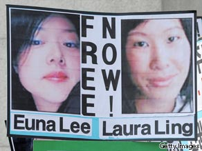 A file picture taken on June 4, 2009 shows a South Korean conservative activist holding pictures of US journalists Euna Lee (L) and Laura Ling (R) during a rally in Seoul.
