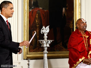 President Barack Obama lights a traditional oil lamp as Sri Narayanachar Digalakote, Hindu Priest from the Sri Siva Vishnu Temple in Maryland, chants in observance of Diwali, or the 'Festival of Lights.'