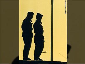 Two East German border guards atop the Berlin Wall look westward