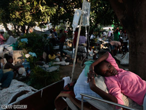 A girl rests at a makeshift outdoor recovery ward outside the morgue and main hospital in Port-au-Prince.