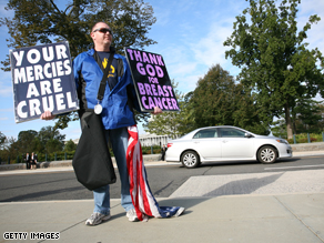 Timothy Phelps, a member of the Westboro Baptist Church from Topeka, Kansas, stands with banners in front of the US Supreme Court on October 6, 2010 in Washington,DC.