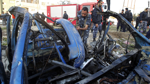 A Hamas policeman inspects the remains of a vehicle targeted by an Israeli airstrike in Gaza City.