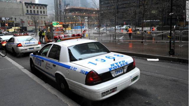 NYPD officers watch as workers clean Zuccotti Park on Sunday after demonstrators were cleared out on Saturday.