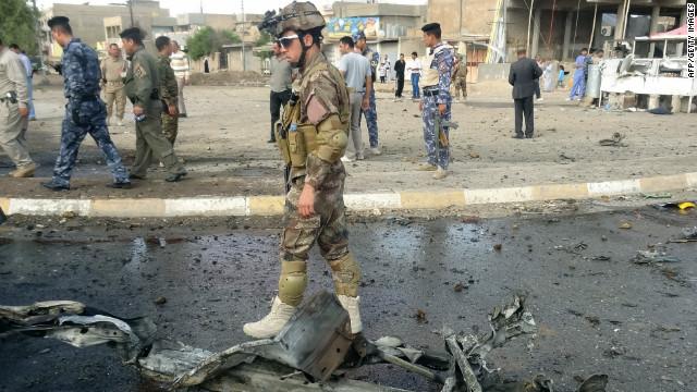 Un soldado iraquí camina residuos pasado en el escenario de dos coches bomba en la norteña ciudad rica en petróleo de Kirkuk el 19 de abril de 2012.