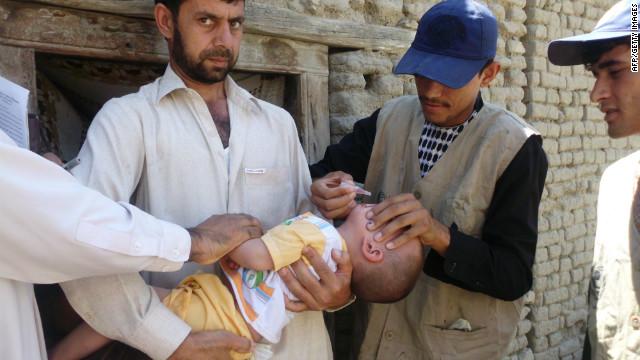 Afganos empleados del Ministerio de Salud administrar la vacuna contra la polio se reduce a un niño en la provincia de Laghman el 11 de junio de 2012.