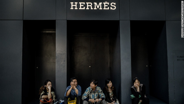 Chinese visitors from the mainland sit in front of a luxury shop in Hong Kong in September.