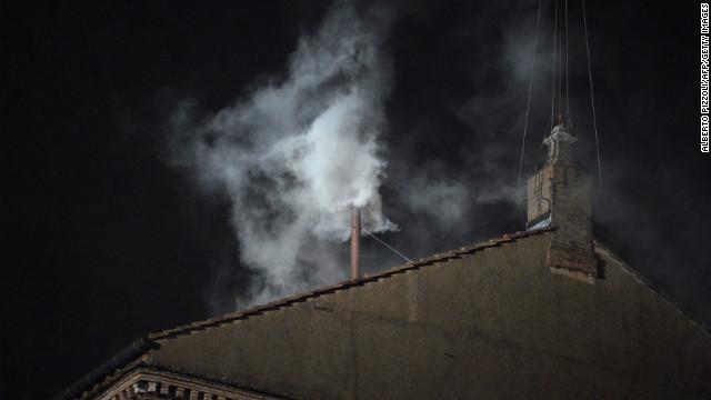 El humo blanco se eleva de la chimenea en el techo de la Capilla Sixtina.