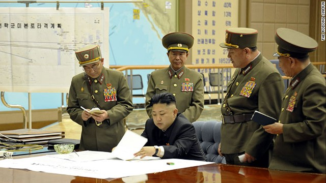 Kim Jong Un is briefed by his generals in this undated photo.