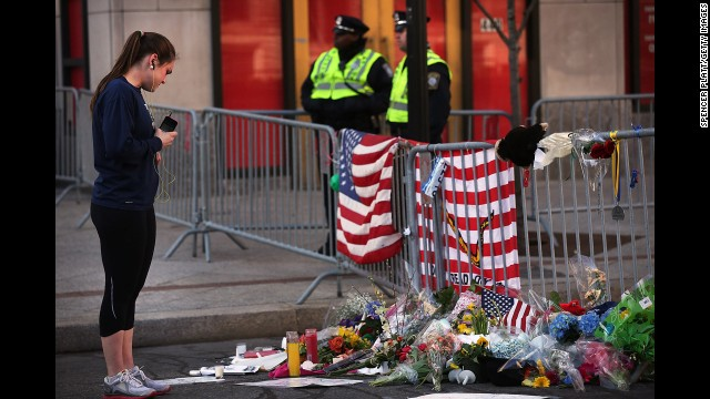 A woman looks at memorials left at the scene of the Boston Marathon explosions.
