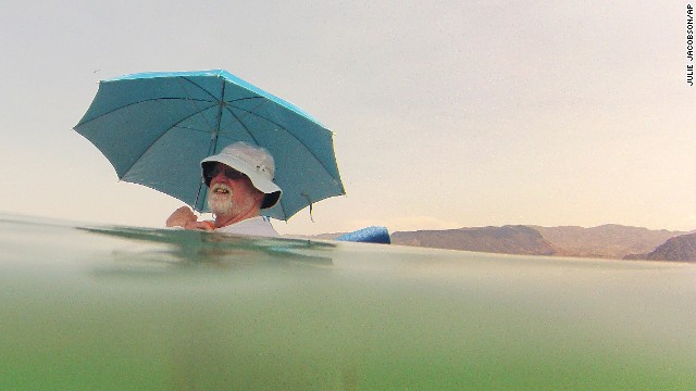 Mike Bouse shades himself with an umbrella as he floats in the water at Lake Mead near Boulder City, Nevada, on Saturday, June 29. Triple-digit temperatures have stifled the Southwest and aren't expected to relent until Tuesday.