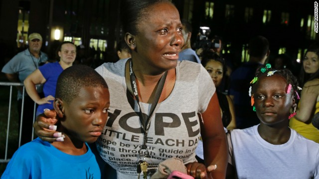 Darrsie Jackson cries and comforts her children Linzey Stafford, left, 10, and Shauntina Stafford, 11, outside the courthouse on July 13.