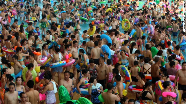 Mass crowds of people attempt to cool off at a water park in Suining, Sichuan province on Saturday, July 27, amid a record heat wave hitting 19 provinces and regions in China.