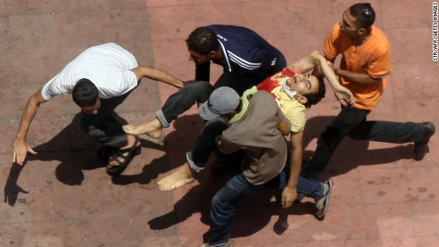 Morsy supporters carry a wounded man during clashes with riot police in Cairo on August 14.