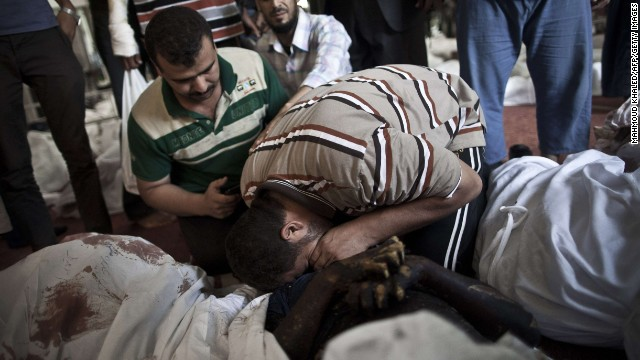 Egyptians mourn over a body wrapped in shrouds at a Cairo mosque August 15.