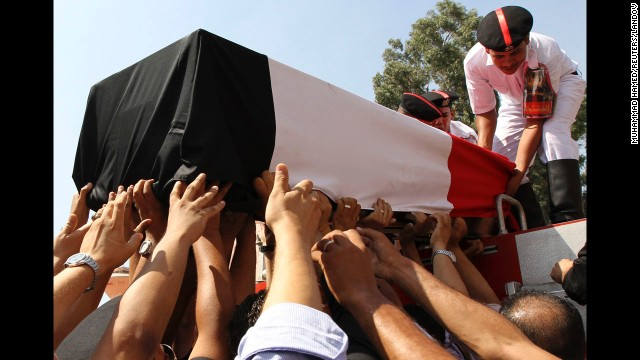 People reach for a coffin on Thursday, August 15, during a funeral for policemen killed during a crackdown at two protest camps in support of ousted President Mohamed Morsy yesterday in Cairo, Egypt. Ferocious clashes on Wednesday, August 14, reportedly left more 500 people dead across Egypt, and authorities have declared a monthlong state of emergency. The recent string of violence began when Egyptian security forces stormed two makeshift camps to clear out Morsy supporters. Look back at Egypt after the coup.