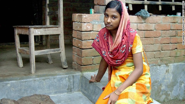 Moyna sits outside her home in the town of Kalora, Bangladesh. As a 14-year-old, she found herself working in an Indian brothel after being tricked into believing she had taken a job in a steel factory.
