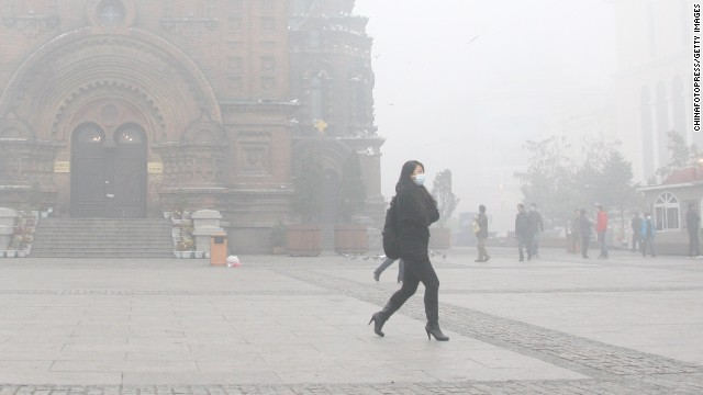 A woman wearing a mask walks along a road as smog engulfs Harbin, China, on Tuesday, October 22. Expressways, schools and an airport were closed after smog disrupted one of northeast China's most heavily populated areas.