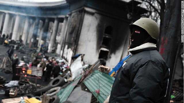 An anti-government protester stands guard on a barricade in central Kiev on Sunday.