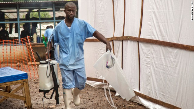A health worker at the Kenema Government Hospital carries equipment used to decontaminate clothing and equipment on August 9.