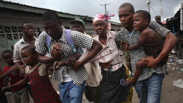 Family members of West Point district commissioner Miata Flowers flee the slum in Monrovia while being escorted by the Ebola Task Force on Wednesday, August 20.