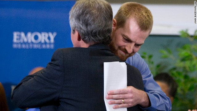 Brantly, right, hugs a member of the Emory University Hospital staff after being released from treatment in Atlanta.