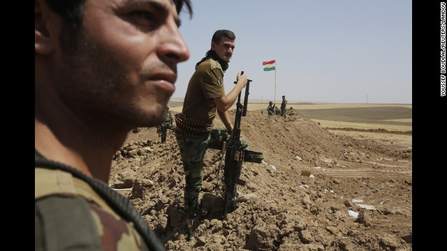 Kurdish Peshmerga forces stand guard at their position in the Omar Khaled village west of Mosul on Sunday, August 24.
