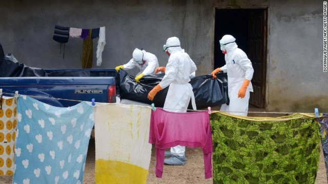 Medical workers from the Liberian Red Cross carry the body of an Ebola victim Thursday, September 4, in Banjol, Liberia.