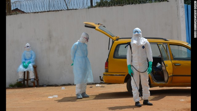Health workers in protective suits work outside an Ebola treatment center in Monrovia on September 23.