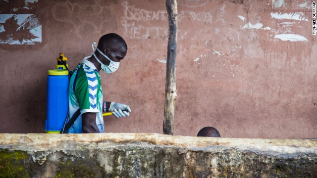 A health worker in Freetown, Sierra Leone, sprays disinfectant around the area where a man sits before loading him into an ambulance on Wednesday, September 24.