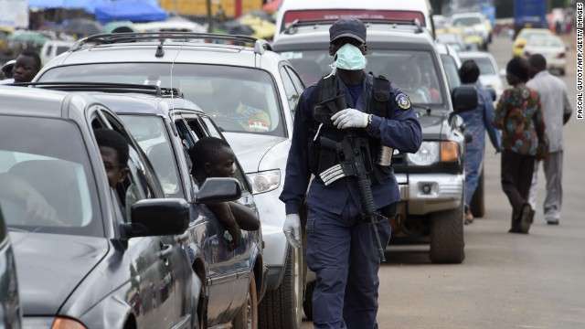 A police officer patrols a road in Monrovia on September 27 after a body was found in the center of the city.