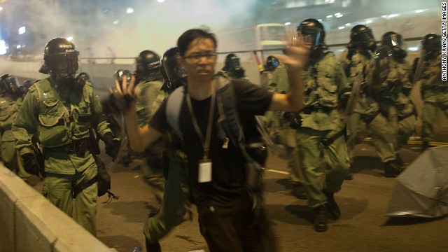 """Demonstrators disperse as tear gas is fired during a protest on September 28. There is an """"optimal amount of police officers dispersed"""" around the scene, a Hong Kong police representative said."""