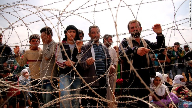 Syrian Kurds wait behind border fences to cross into Suruc on September 28.