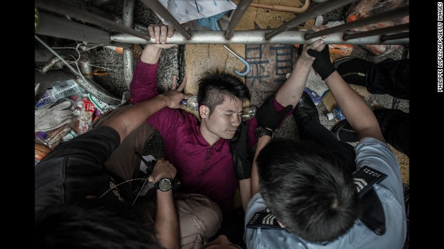 Police try to pry a man from a fence guarded by pro-democracy demonstrators on October 3.