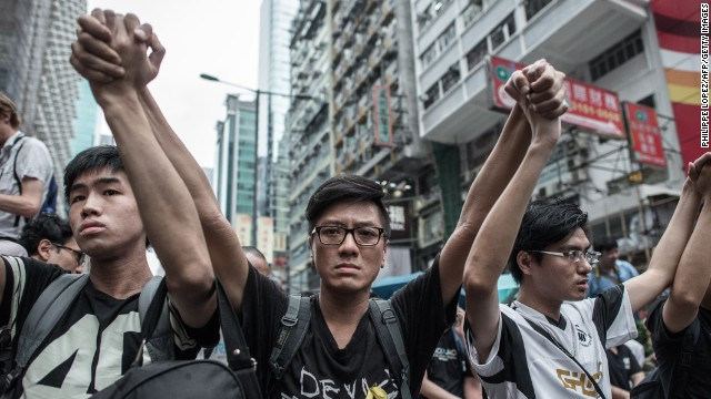 Pro-democracy protesters raise their arms in a sign of nonviolence as they protect a barricade from rival protest groups in the Mong Kok district of Hong Kong on October 4.