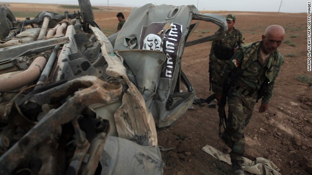 Peshmerga fighters inspect the remains of a car that reportedly belonged to ISIS militants and was targeted by a U.S. airstrike in the village of Baqufa, north of Mosul, on August 18.