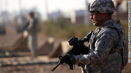 An American soldier stands guard at the Taji base complex which hosts Iraqi and US troops and is located thirty kilometres north of the capital Baghdad on December 29, 2014. T