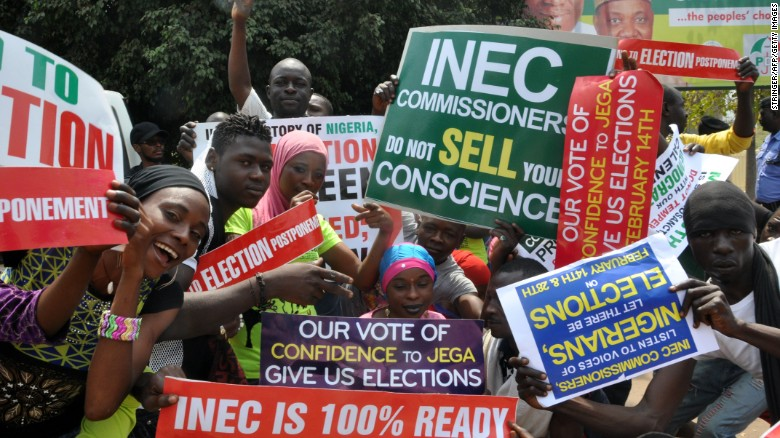 People in Abuja hold signs to protest the postponement of the elections.