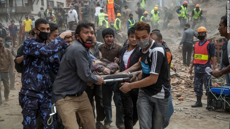 Caption:KATHMANDU, NEPAL - APRIL 25: Emergency rescue workers carry a victim on a stretcher after Dharara tower collapsed on April 25, 2015 in Kathmandu, Nepal. More than 100 people have died as tremors hit Nepal after an earthquake measuring 7.9 on the Richter scale caused buildings to collapse and avalanches to be triggered in the Himalayas. Authorities have warned that the death toll is likely to be much higher. (Photo by Omar Havana/Getty Images)