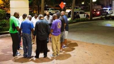Worshipers gather to pray in a hotel parking lot across the street from the scene of the shooting. Every Wednesday evening, the church holds a Bible study in its basement.