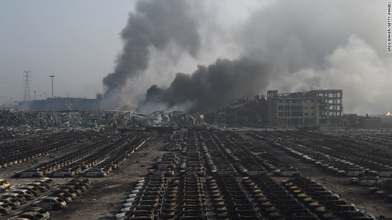 Smoke billows behind rows of burnt out cars at the site of a series of explosions in Tianjin, northern China.
