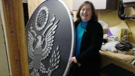 Martina Polt holds up the new seal for the U.S. Embassy in Havana. It has been kept in a locked room in the basement.