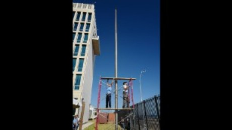 Workers rush to finish the flagpole outside the U.S. Embassy.
