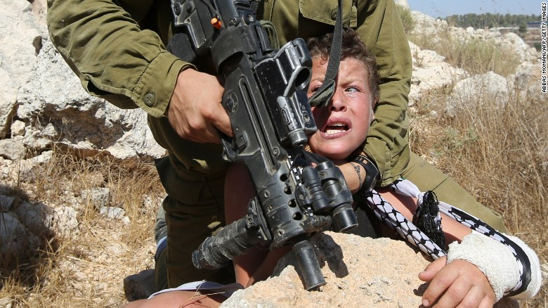 An Israeli soldier holds down a Palestinian boy during a protest in the West Bank on Friday.