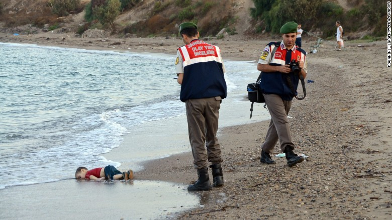 """Authorities stand near Aylan's lifeless body on Wednesday, September 2. This photo went viral around the world, often with a Turkish hashtag that means """"Flotsam of Humanity."""""""