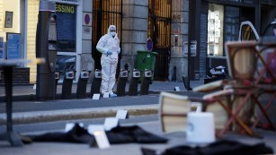 A forensic scientist works near Cafe Bonne Biere in Paris on Saturday, November 14, following a series of coordinated attacks in Paris the night before that killed scores of people. ISIS has claimed responsibility.