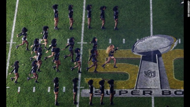 Beyonce and her dancers perform on the field.