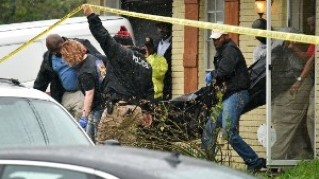 Vicksburg police carry out the body of escaped murder suspect Rafael McCloud into a coroner's vehicle after he was shot by a homeowner during a hostage situation in Vicksburg, Miss.