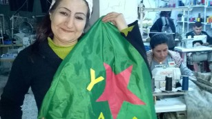The YPJ flag belongs to the women's defence units and was 'modelled' by a worker in a sewing collective.
