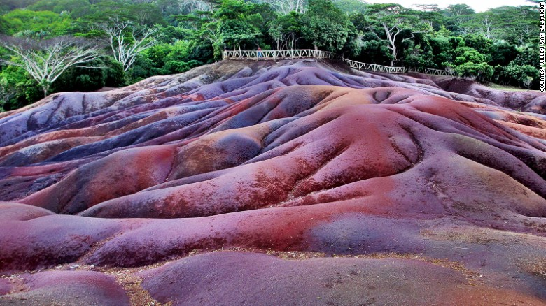 The colorful sand dunes in Charamel, Mauritius, are one of several places on Earth that resemble alien worlds. The striped sands are formed from volcanic rock but they remain a scientific mystery.